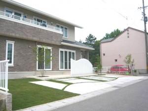 芝生の庭と土間コンクリートの駐車場